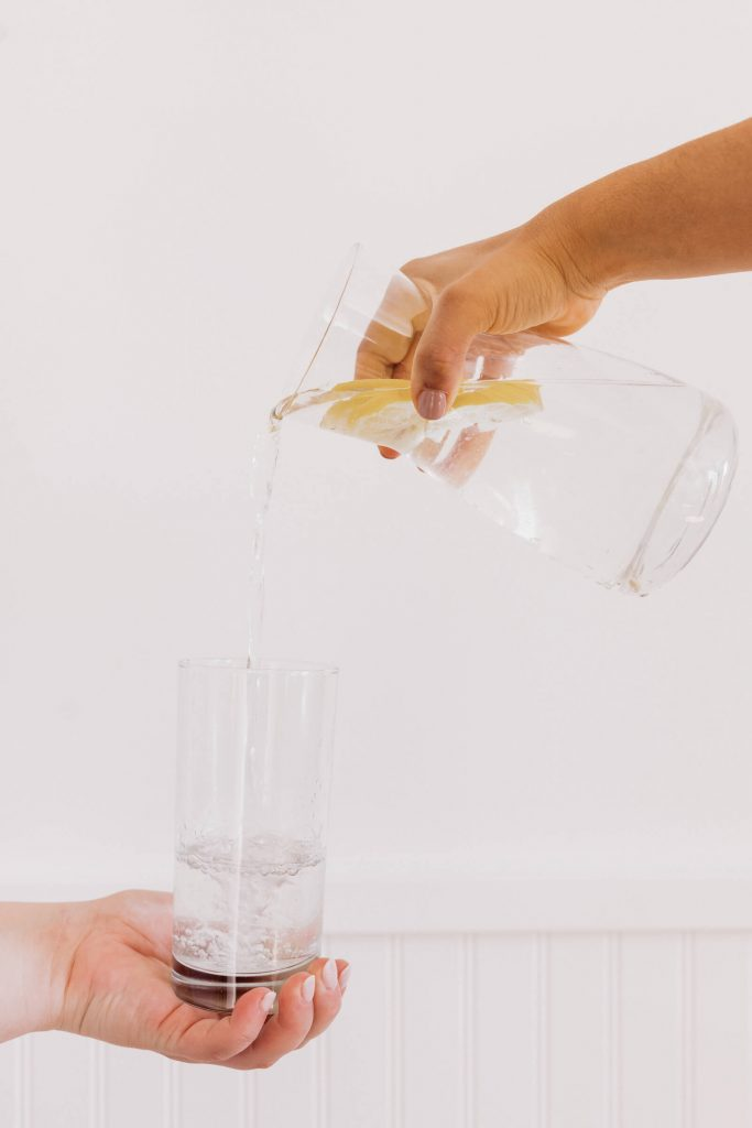 Woman pouring lemon water.